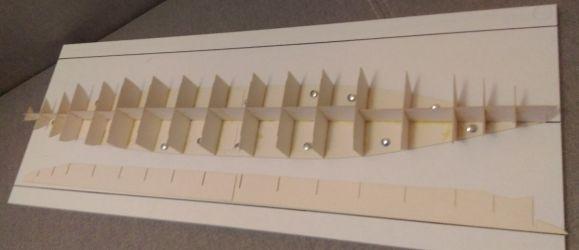 Wodnicę wraz z górnymi wręgami przymocowałem do deski roboczej za pomocąpinesek. Na desce oczywiście naniosłem prostą linię wyznaczającą oś.