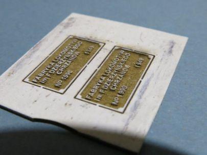 tabliczka z przemalowanym napisem na biało za pomocą walca metalowego